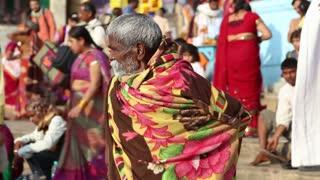 VARANASI, INDIA - 22 FEBRUARY 2015: Indian man covered in blanket talking at the street in Varanasi.