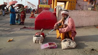 VARANASI, INDIA - 22 FEBRUARY 2015: Indian man hypnotising a snake with music at street in Varanasi.