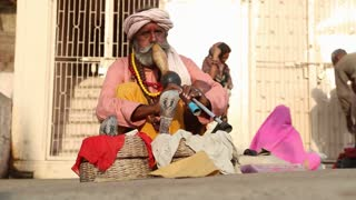 VARANASI, INDIA - 22 FEBRUARY 2015: Indian man hypnotising cobra with music at street in Varanasi.