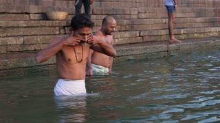 VARANASI, INDIA - 22 FEBRUARY 2015: Indian men bathing at Ganges river in Varanasi.