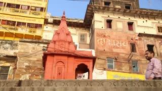 VARANASI, INDIA - 22 FEBRUARY 2015: Low angle view of people passing by street buildings in Varanasi.