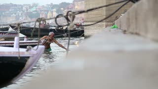 VARANASI, INDIA - 22 FEBRUARY 2015: Man coming out of Ganges river and climbing up the ghat.