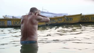 VARANASI, INDIA - 22 FEBRUARY 2015: Man praying in Ganges river in Varanasi at sunset.