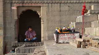 VARANASI, INDIA - 22 FEBRUARY 2015: Man praying in the yard of a temple in Varanasi.
