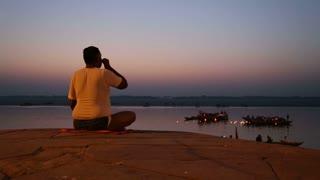 VARANASI, INDIA - 22 FEBRUARY 2015: Man praying with high angle view on boats sailing at Ganges river.