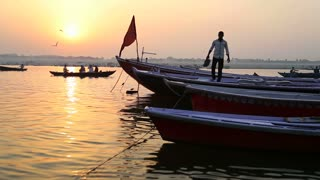 VARANASI, INDIA - 22 FEBRUARY 2015: Man walking on the boat in the bay of Ganges river at sunset.