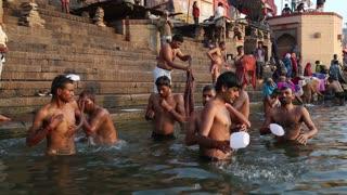 VARANASI, INDIA - 22 FEBRUARY 2015: Men bathing in the Ganges river in Varanasi.