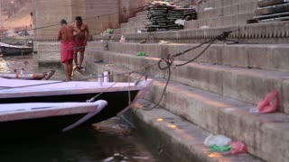 VARANASI, INDIA - 22 FEBRUARY 2015: Men bathing on the ghats of Ganges river in Varanasi, surrounded with boats.