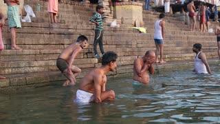 VARANASI, INDIA - 22 FEBRUARY 2015: Men bathing on the ghats of Ganges river in Varanasi.