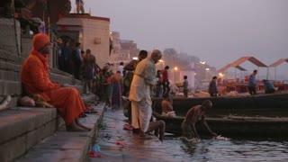 VARANASI, INDIA - 22 FEBRUARY 2015: People at ghat of Ganges river in Varanasi at sunset.