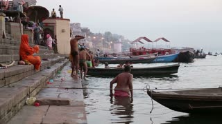 VARANASI, INDIA - 22 FEBRUARY 2015: People bathing by the ghats of Ganges river in Varanasi.