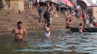 VARANASI, INDIA - 22 FEBRUARY 2015: People bathing on the ghats of Ganges river in Varanasi.
