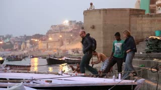 VARANASI, INDIA - 22 FEBRUARY 2015: People climbing to the tourist boat on Ganges river in Varanasi.