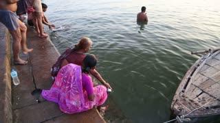 VARANASI, INDIA - 22 FEBRUARY 2015: Women sitting on ghats of Ganges river in Varanasi.