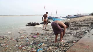 VARANASI, INDIA - 25 FEBRUARY 2015: Group of boys playing at dirty shore of Ganges.