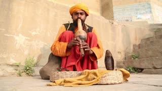 VARANASI, INDIA - 25 FEBRUARY 2015: Indian man hypnotising a snake with music at street in Varanasi.