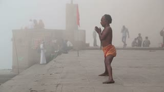 VARANASI, INDIA - 25 FEBRUARY 2015: Man practicing yoga at shore of Ganges, with people passing.