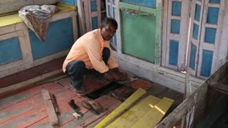 VARANASI, INDIA - 25 FEBRUARY 2015: Man scrubbing a material at floor of workshop in Varanasi.