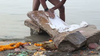 VARANASI, INDIA - 25 FEBRUARY 2015: Man scrubbing clothes on a stone at shore of Ganges river.
