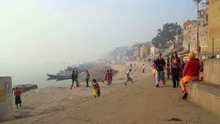 VARANASI, INDIA - 25 FEBRUARY 2015: People passing at dock in Varanasi, with Ganges river in background.
