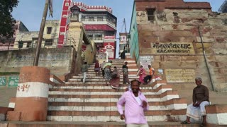 VARANASI, INDIA - 25 FEBRUARY 2015: People walking up the city stairs in Varanasi, with buildings in background.