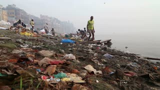 VARANASI, INDIA - 25 FEBRUARY 2015: View on people going through waste at dirty shore of river Ganges.