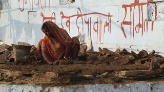 VARANASI, INDIA - 25 FEBRUARY 2015: Woman kneading mud at Ganges bay, with graffiti on wall in background.