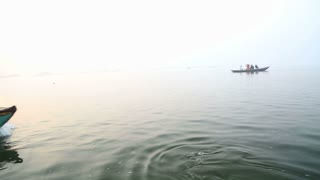 VARANASI, INDIA - 26 FEBRUARY 2015: Boat full of people passing down the river fastly.