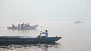 VARANASI, INDIA - 26 FEBRUARY 2015: Boats, with men rowing and travelers sitting, going down the river Ganges.