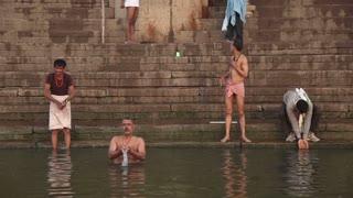 VARANASI, INDIA - 26 FEBRUARY 2015: Men bathing and praying at Ganges river ghat in Varanasi.