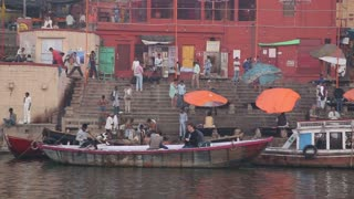 VARANASI, INDIA - 26 FEBRUARY 2015: Panoramic view of ghats with people and boats passing at Ganges river.