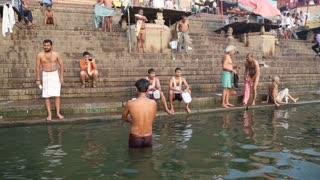 VARANASI, INDIA - 26 FEBRUARY 2015: People bathing and sitting at ghat of Ganges river in Varanasi.