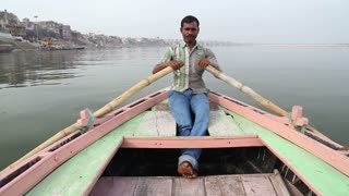 VARANASI, INDIA - 26 FEBRUARY 2015: Portrait of man rowing in boat at Ganges, with cityscape in background.