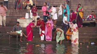 VARANASI, INDIA - 26 FEBRUARY 2015: Women and men at Ganges river ghat in Varanasi.