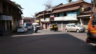 Vehicles driving down the busy road in Goa in different directions.
