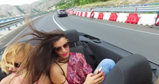 Attractive woman riding in the backseat of convertible and typing on phone