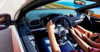 Attractive woman turning steering wheel driving friends convertible car, graded