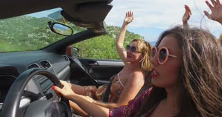 Attractive woman with round frame pink sunglasses driving friends in convertible