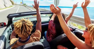 Back view of friends waving arms driving in convertible, color graded