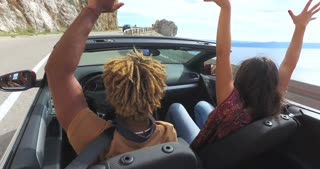 Back view of friends waving arms driving on coastal road in red convertible