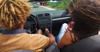 Back view of handsome black men driving his friends in convertible