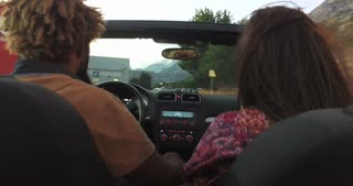 Back view of mixed race couple driving in convertible