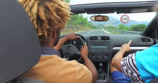 Back view of two men driving in convertible on coastal highway
