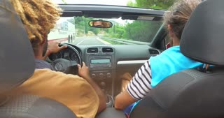 Back view of two men partying while driving in convertible on coastal highway