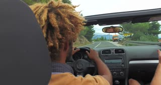 Back view of two young male friends driving in convertible on coastal highway