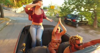 Beautiful brunette sitting on hood of convertible dancing riding with friends