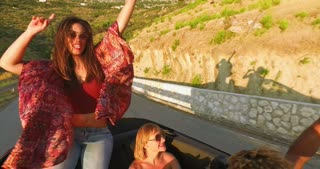 Beautiful brunette sitting on hood of convertible riding with her friends