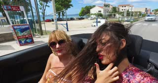 Beautiful girl adjusting hair while riding in windy the back seat of convertible