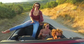Beautiful young brunette sitting on hood of convertible car riding with friends