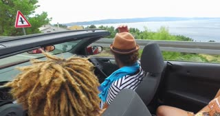 Black handsome man driving his friends in convertible